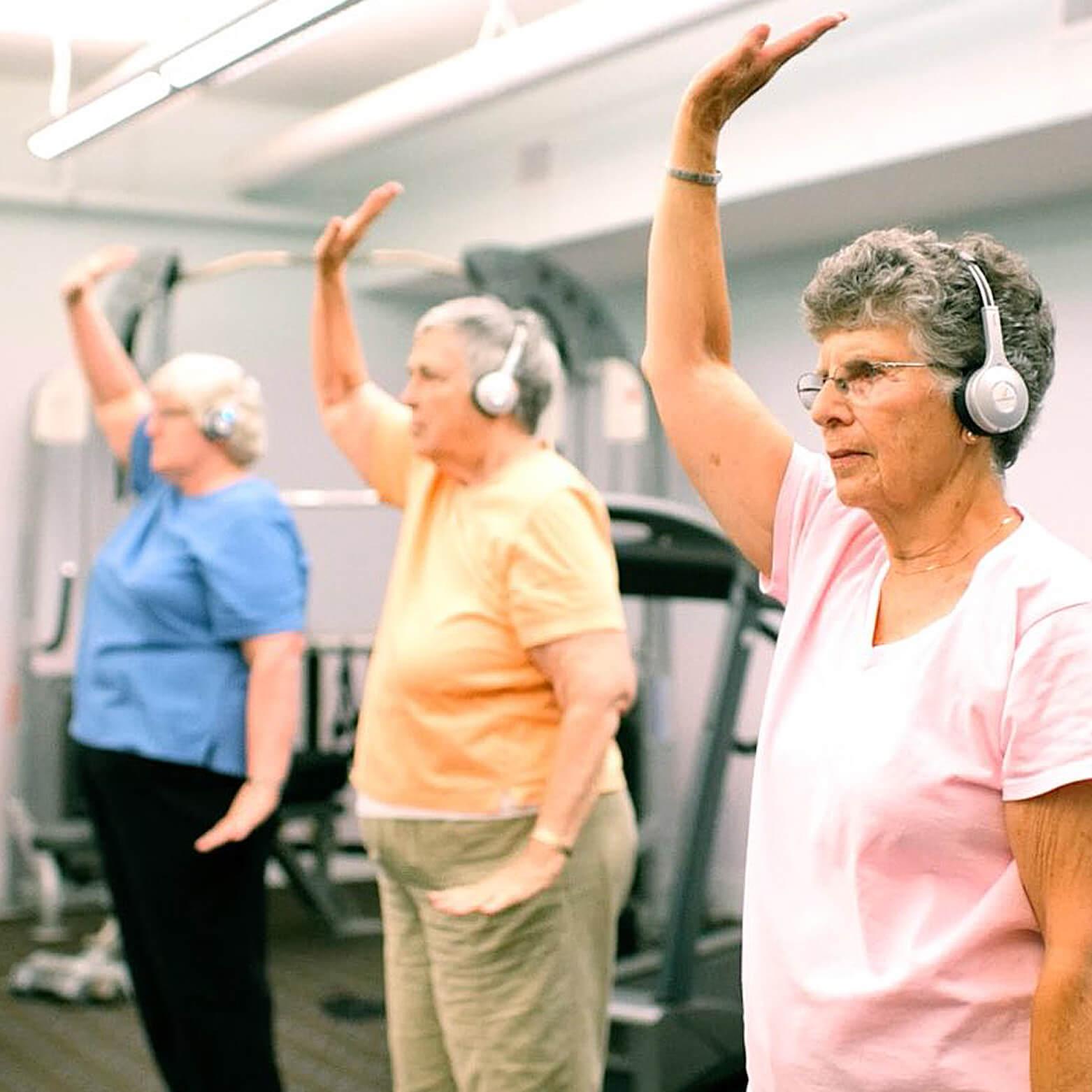 Senior residents doing tiachi yoga using Eversound headphones