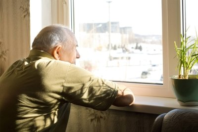 Lonely elderly man staring out of a window