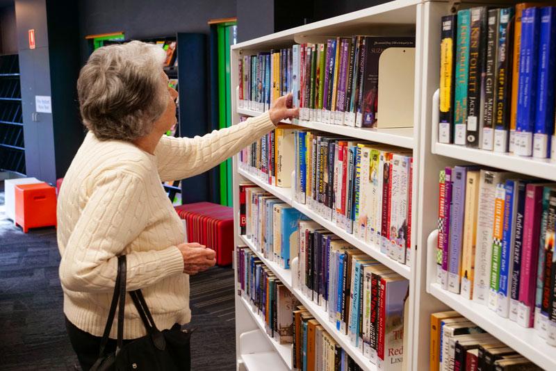 senior woman looking through books